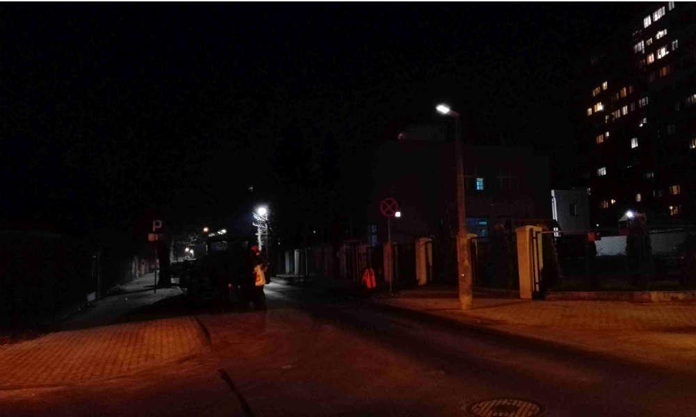 """Ulica PCK w Toruniu. Na zdjęciu skrzyżowanie oświetlone ciepłym światłem z ulicy Dekerta, gdzie jeszcze w użyciu są lampy sodowe. Lampa LED """"świeci"""", ale nie działa. Piesi (tak, są na tym zdjęciu) stają się widoczni dopiero w świetle reflektorów samochodowych Fot. Anna Zglińska"""