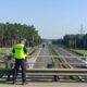 Policjant mierzący bezpieczną odległość między pojazdami na węźle Szczecin Dabie. Fot. Policja